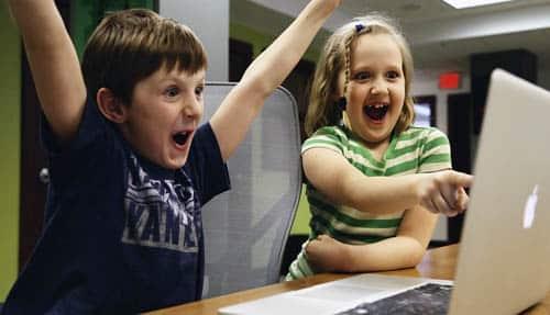 Niños disfrutan frente al ordenador portátil Mac Apple. Cómo encontrar los mejores chollos en móviles en Black Friday