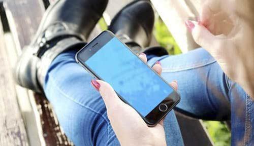 Cómo encontrar los mejores chollos en móviles en Black Friday. Chica visualiza pantalla el móvil.